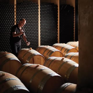 Man tapping wine barrels in rows in a wine a cellar