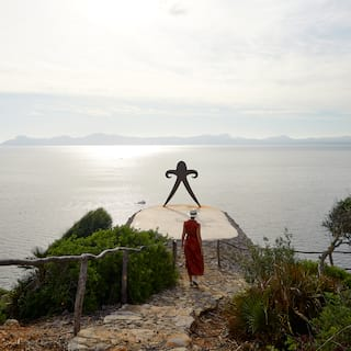 Lady in a red dress walking down stone steps towards a plateau overlooking the sea