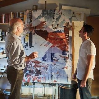 Artist in a studio describing a modern art painting on an easel to a guest