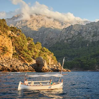 A small wooden sailing boat bobbing on coastal waters with mountains beyond