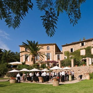 Guests at a garden party among lush gardens outside a stone-built Spanish villa