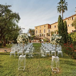 Rows of chairs set either side of an aisle for a wedding in a lush Spanish garden