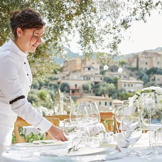 Waitress setting an outdoor banquet table for a wedding