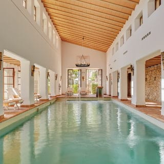 Indoor spa pool with a sloped wood-panelled ceiling and exposed stone walls