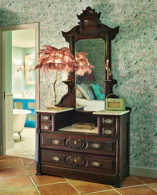 Close-up of an antique vanity table and mirror against blue floral wallpaper