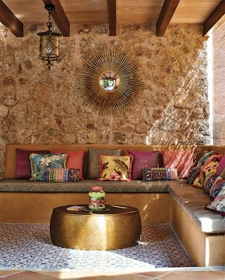 Corner banquette sofa with vibrant cushions and a gold drum coffee table