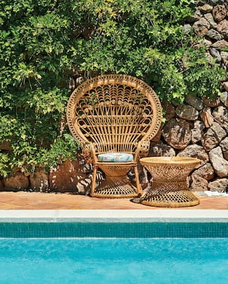 Close-up of a stylish bamboo chair and matching coffee table beside an outdoor pool