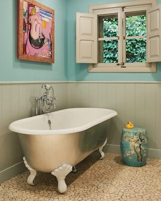 Rolltop standalone bathtub in a bathroom with wooden wallpanels and blue walls