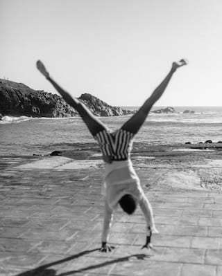 Black and white photo of a person somersaulting on a beach