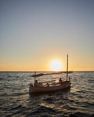 Sailing boat bobbing on waves at sunset