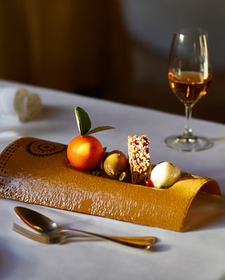 Close-up of a dessert dish served on a curved platter next to a glass of dessert wine