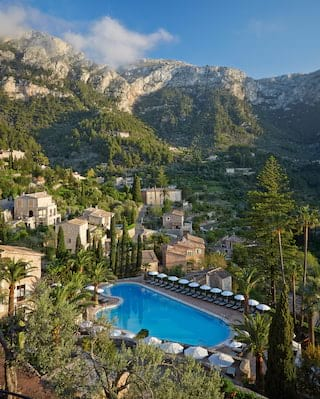 Aerial view of an outdoor pool surrounded by sunbeds overlooking a Mallorcan village
