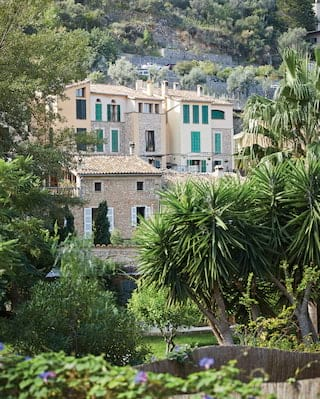 View of a stone-built Mallorcan house with green window shutters among lush palms