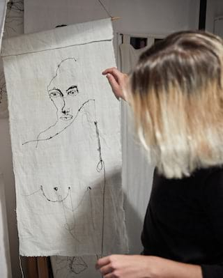 Lady holding up a sewn portrait of a lady on a textile canvas