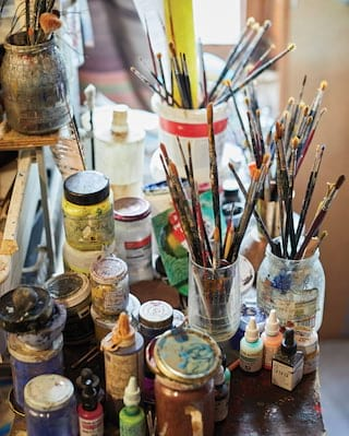 Close-up of an assortment of paint brushes in pots on a wooden desk