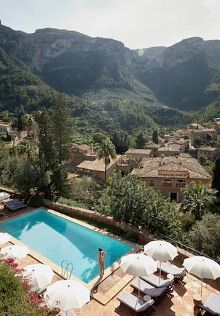 Aerial view of an outdoor pool and the Tramuntana Mountains beyond