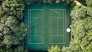 Birds-eye view of two tennis courts side-by-side and surrounded by jungle