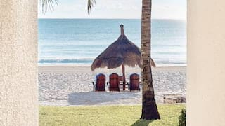 Thatched parasol over three sunbeds overlooking white sands and a calm sea