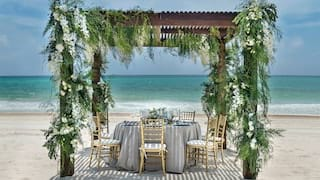 Shaded circular table on white sands under a pergola coated in flowers