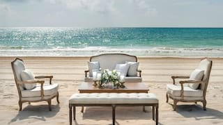 White-cushioned lounge seating with a floral center-table on the beach