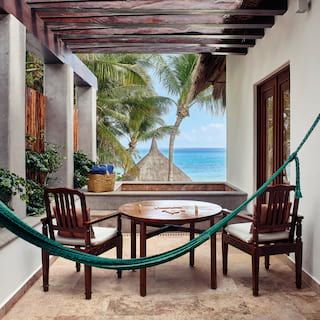 Blue hammock across a terrace seating area overlooking the Caribbean Sea