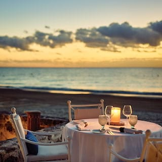 Candlelit beach restaurant table overlooking the Caribbean Sea at sunset