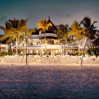 Glowing beach restaurant at night, viewed from across the water