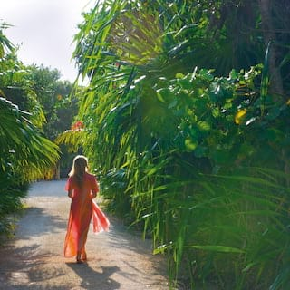 Lady in a red sun dress strolling on a path among lush jungle foliage