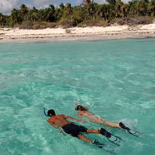A couple holding hands as they snorkel under a crystal clear sea surface