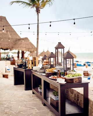 Beach terrace with dark wooden tables laden with buffet salads