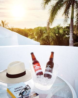 Close-up of a circular table with chilled beer, Panama hat and book