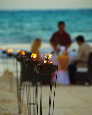 Lanterns in a row leading to a couple at a table for two on the beach