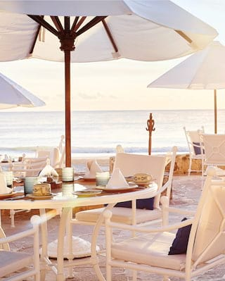Beach restaurant at sunset with white furniture and parasols