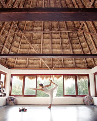 Lady in a yoga pose in a light and airy palapa studio