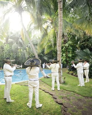 Traditional mariachi band playing among jungle gardens on a sunny day