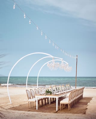 Empty wedding banquet table on a sunny beach with overhanging chandeliers