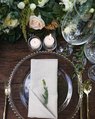 Wedding place setting with a white linen napkin on a clear glass plate