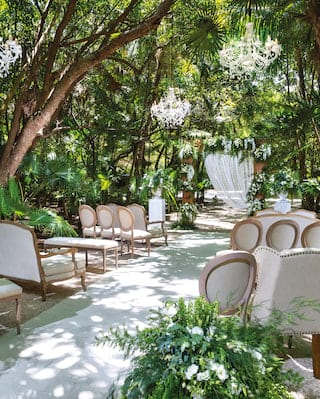 Outdoor wedding aisle with armchair seating under chandeliers, in the jungle