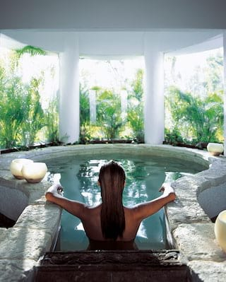 Lady relaxing in a spa hot tub with jungle views through the windows
