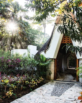 Stone pathway leading to an elegant stone hut among lush tropical gardens