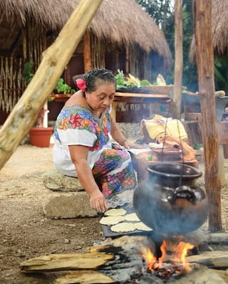 Lady in a floral dress cooking over a fire