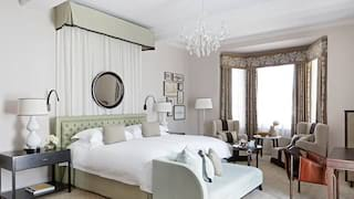 Hotel room with light green accents and beautiful bay window