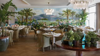 Glamorous bistro with Table Mountain wall mural, modern chandeliers and palm plants