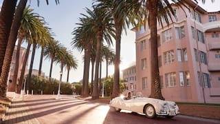 White classic car on a palm-lined boulevard next to a pink facade hotel