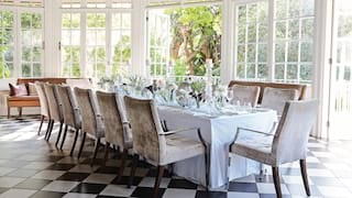 Wedding banquet table in a light-filled conservatory with checkerboard tiles