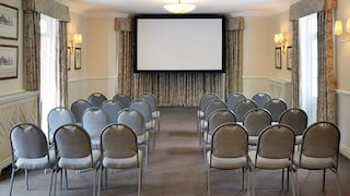 Rows of event chairs facing a projector screen at the end of a conference room