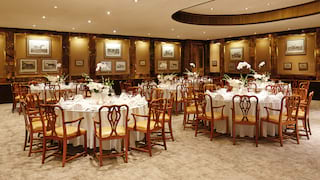Elegant room lined with artwork with circular tables set for a wedding