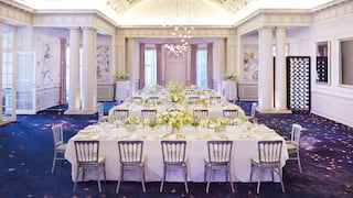 Large elegant ballroom with star patterned carpet and banquet tables set for a wedding