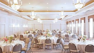 Large ballroom set with circular tables for a wedding under crystal chandeliers