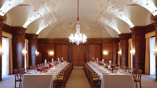 Grand wood-panelled room with ornate cornicing and single crystal chandelier